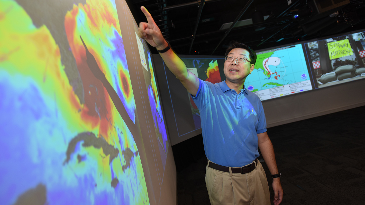 Roy He points at a weather map